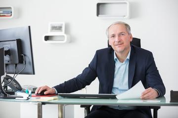 Älterer Geschäftsmann als Chef am Schreibtisch