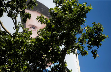 A poster of People's Party (PP) candidate Pablo Casado is seen through the branches of a tree on the facade of People's Party headquarters a day after Spain's general election, in Madrid