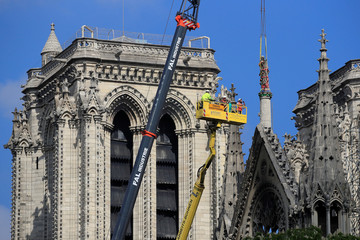 Men work on a statue at Notre-Dame Cathedral, after a massive fire devastated large parts of the gothic structure in Paris