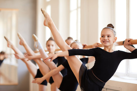 Waist up portrait of smiling little girl stretching legs standing at bar in ballet class, copy space