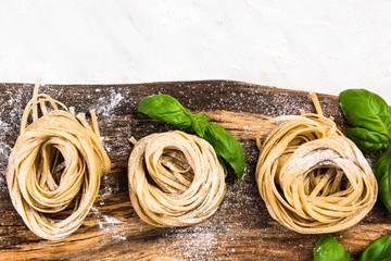 Raw uncooked italian tagliatelle pasta on wooden board