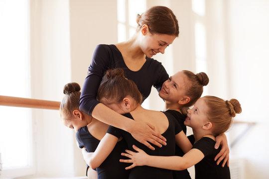 Group of little girls hugging ballet teacher in studio lit by warm sunlight, copy space