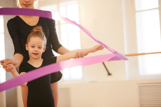 Little girl doing gymnastics moves with ribbon in studio lit by warm sunlight, copy space