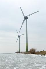 Large windmills on a dyke of the frozen Gouwsea near the village of Uitdam.