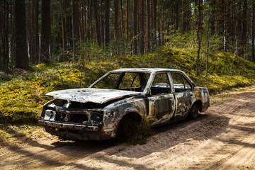 Fully burnt car in the forest in spirng on sandy road