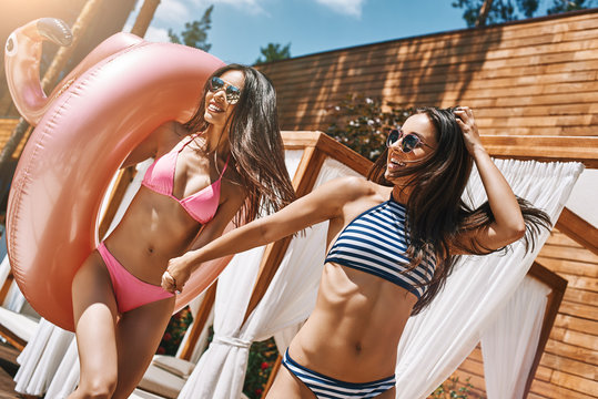 Just having fun! Two sexy and beautiful young women in swimwear and sunglasses having fun together outdoors while one of them carrying inflatable ring.