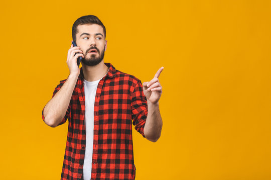 Portrait of an excited young man in casual using mobile phone while pointing finger up isolated over red background.