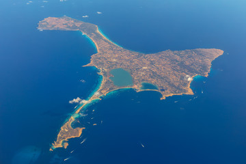 View of the whole island of Formentera from a plane at cruising altitude with many boats and ships on the sea.