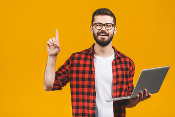 Young bearded man holds laptop and finger point up isolated against yellow background.