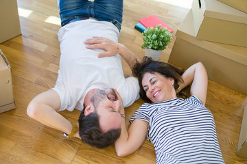 Middle age senior romantic couple lying on the floor, smiling happy for moving to a new house, relaxing and taking a break of packing boxes