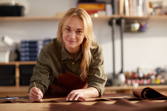 Portrait of female artisan smiling at camera while working with leather in workshop, copy space