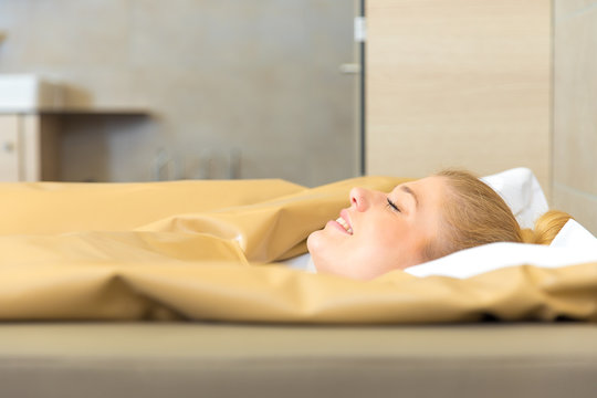young beautiful woman are doing a fango therapie in a wellness area. friends are on the side of the water bed