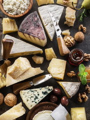 Wall Mural - Assortment of different cheese types on stone background. Top view.