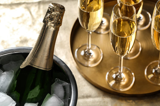 Bottle of champagne in bucket with ice and glasses on table, closeup. Space for text