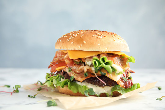 Tasty burger with bacon on table against color background