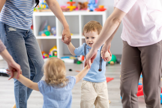Little children and mothers roundelay in daycare