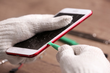 Technician fixing mobile phone at table, closeup. Device repair service