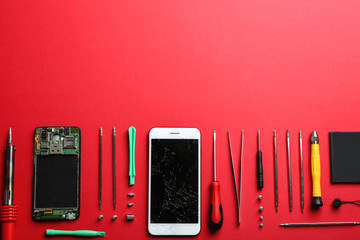Broken mobile phone and repair tools on color background, flat lay. Space for text