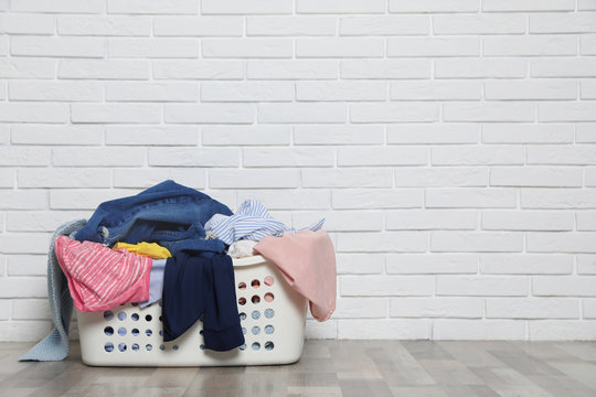 Laundry basket with dirty clothes on floor near brick wall. Space for text