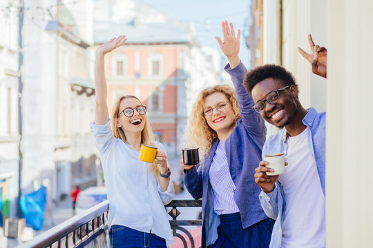 Group of three multiethnic business people friends coworkers chatting meeting, drinking coffee, sharing positive emotions on balcony in sunny morning.