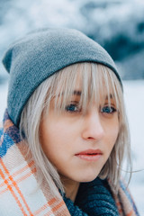 Portrait of a beautiful girl in a hat and poncho in the mountains in winter, adventure and travel