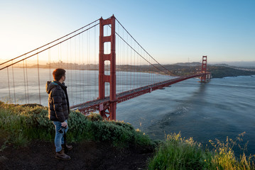 Asian man photographer and tourist enjoy looking at Golden Gate Bridge during sunrise, Iconic bridge and famous landmark of San Francisco, California, USA. Travel photography concept