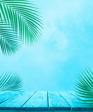 Empty of blue wood table top with coconut leaf on soft sky background.For montage product display or design keyvisual layout