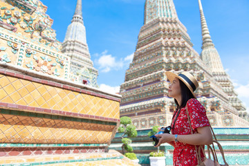 Wall Mural - Asian woman is enjoy traveling inside Wat Pho in Bangkok, Thailand during summer.