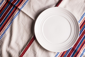 Empty white plate on a napkin, top view. Image with copy space. Kitchen table with a towel and a plate - top view with copy space.