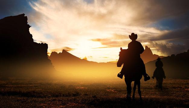 Cowboys on horseback at sunset