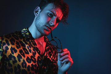 Fashion art neon light studio portrait of stylish man model with leopard shirt and glasses. Glamour light.