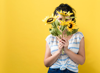 Young woman with sunflowers on a yellow background