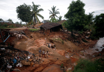 Children play outside a house, collapsed in the aftermath of Cyclone Kenneth, at Wimbe village in Pemba