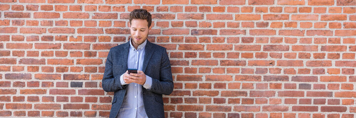 Businessman sms texting phone app in city street on brick wall background. Business man holding smartphone in smart casual wear standing. Urban young professional lifestyle.