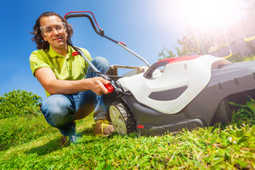 Man cleaning grass box of electric lawn mower