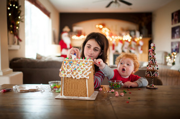 Two kids decorating a gingerbread house for the holidays at home