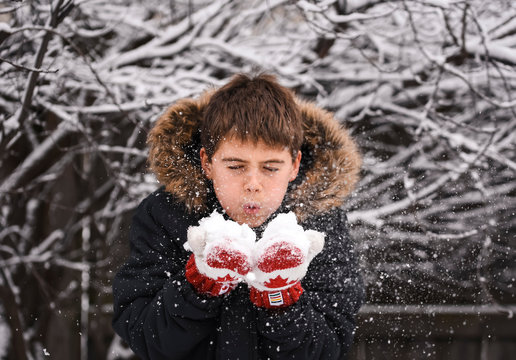 Close up of boy blowing snow off of his mittens with hands together.