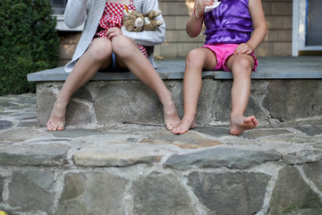 two girls legs and toes sitting on porch steps in shorts