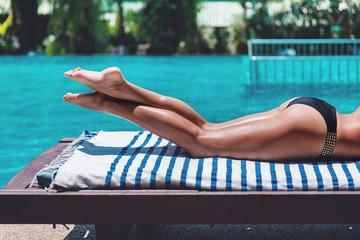 Young slim woman legs in bikini relax near swimming pool in sun lounger