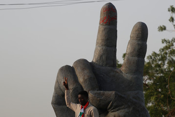 A Sudanese protester makes a victory sign outside the defense ministry compound in Khartoum