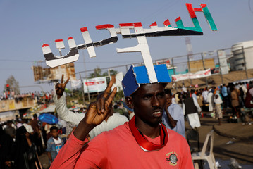 """A Sudanese protester makes a victory sign, wearing a cutout that reads """"Free Sudan"""" in Arabic on his head, during a demonstration outside the defense ministry compound in Khartoum"""