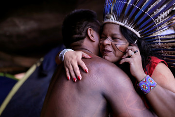 Indigenous Leader Sonia Guajajara embraces a member of her tribe as she talks on her mobile phone at the Terra Livre camp, or Free Land camp, in Brasilia