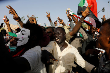 Sudanese protesters make victory signs and chant slogans as they attend a demonstration outside the Defence Ministry compound in Khartoum