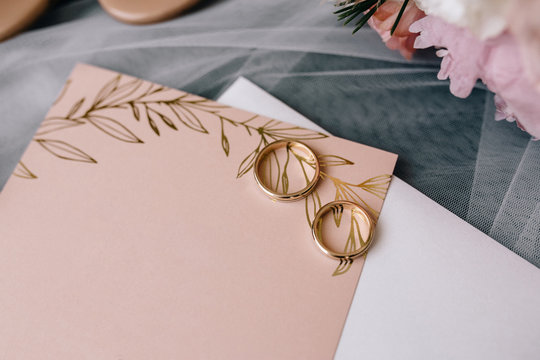Beautiful decorated wedding invitations and wedding rings
