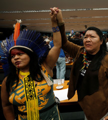 Congresswoman Joenia Wapichana of the Wapixana tribe and Indigenous Leader Sonia Guajajara of the Guajajara tribe raise their hands during a meeting with congressmen during the Terra Livre camp, or Free Land camp, at the National Congress in Brasilia