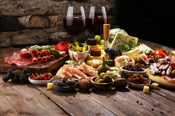 Italian antipasti wine snacks set. Cheese variety, Mediterranean olives, crudo, Prosciutto di Parma, salami and wine in glasses over grunge background. Wall mural