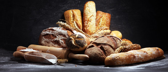 Foto auf Acrylglas Brot Assortment of baked bread and bread rolls on rustic black bakery table background