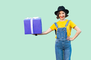 Happy beautiful young girl in hipster wear in denim overalls and black hat standing and holding big heavy gift box with toothy smile with hand on belt, looking at camera. Studio shot, green background Wall mural