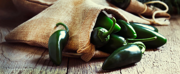 Green jalapeno peppers, old wooden kitchen table background, selective focus