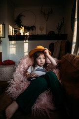 Girl looking out window with yellow hat in home